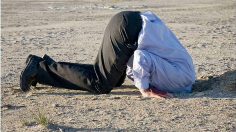 Человек с головой в песке
